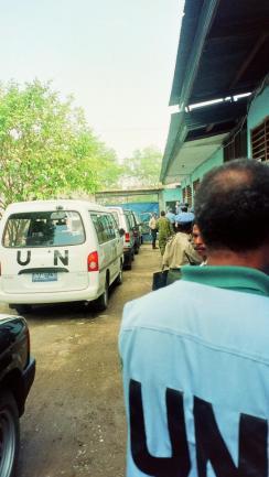UN volunteer in front of vans.