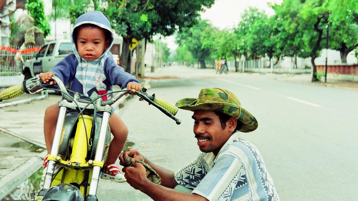 Man holding his kid on a bike.