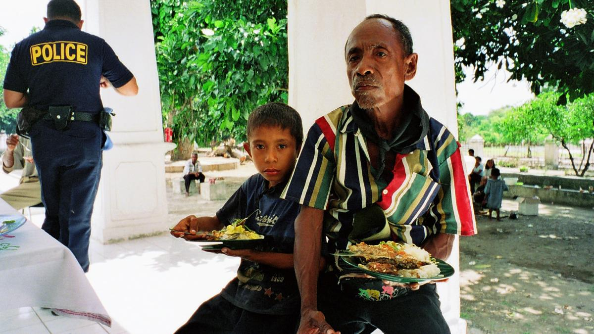 Man eating outside with his son.
