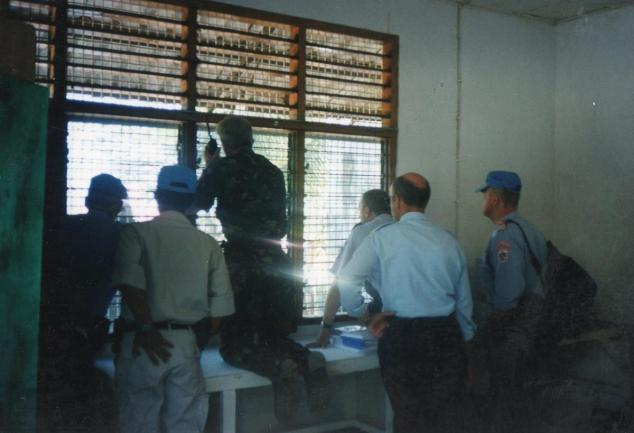 Members of the Maliana UN base looking outside of the window.